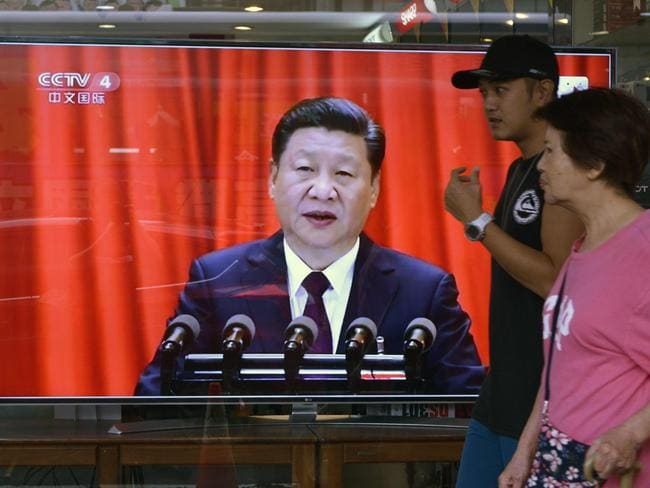Pedestrians walk past a monitor showing a broadcast from Beijing of Chinese leader Xi Jinping delivering a stern warning to Taiwan on October 18, saying that Beijing has the will and power to thwart any attempts at independence. Picture: AFP