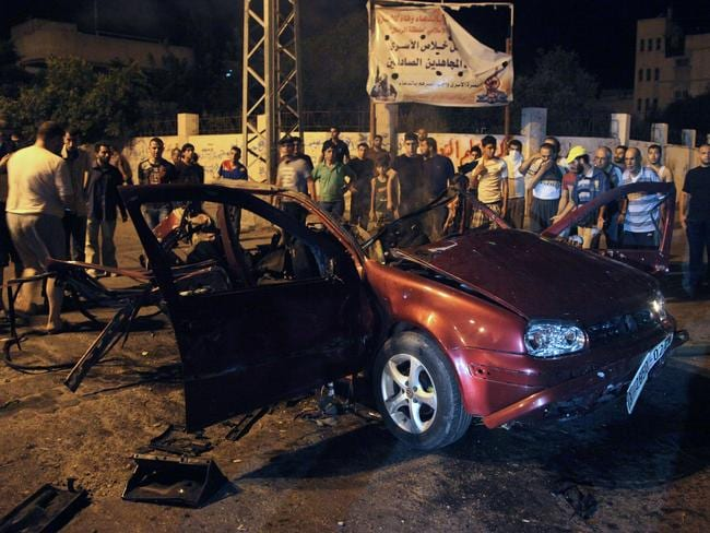More destruction ... people gather around a car after it was hit by an Israeli strike in Gaza. Picture: EZZ AL-ZAANOUN