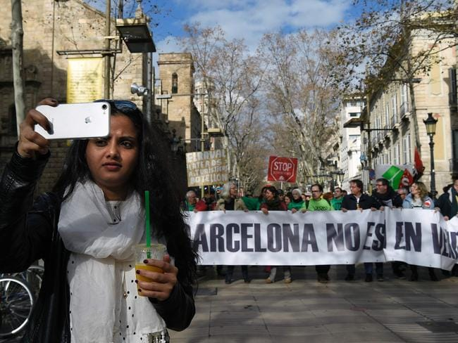 "A tourist takes a selfie in front of a banner that says ""Barcelona is not for sale"" during a demonstration in Barcelona on January 28, 2017. Photo: AFP PHOTO/LLUIS GENE"