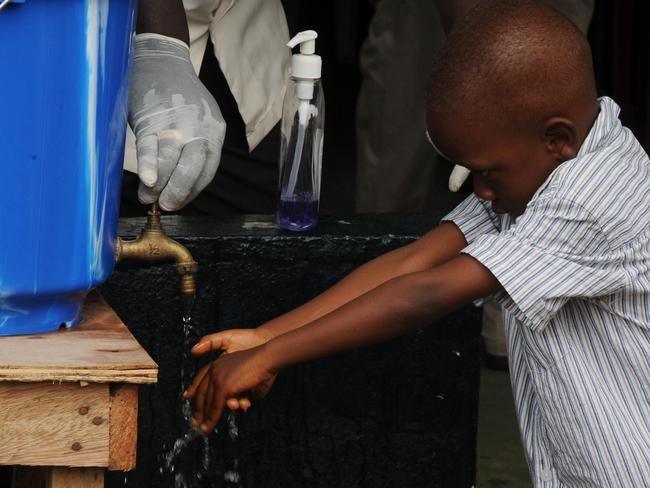 A boy washes his hands before entering a mass on Sunday in Liberia. Pic: AFP.