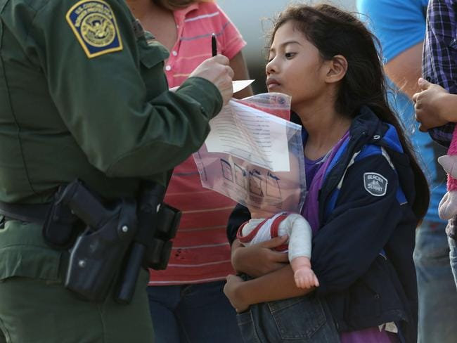 Looking for a new home ... Salvadorian immigrant Stefany Marjorie, 8, watches as a US Border Patrol agent records family information in Mission, Texas. Picture: John Moore
