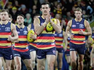 Taylor Walker of the Crows leads his team on to Adelaide Oval during the Round fourteen AFL match between the Adelaide Crows and North Melbourne Kangaroos at Adelaide Oval in Adelaide, Thursday, June 23, 2016 (AAP Image/Ben Macmahon) NO ARCHIVING, EDITORIAL USE ONLY