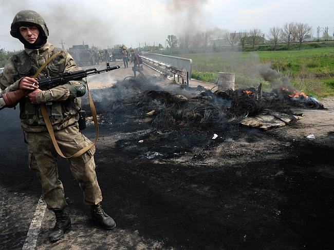 Standing their ground ... a Ukrainian soldier stands guard near a checkpoint which troops seized in the early morning in the village of Andreevka. Picture: VASILY MAXIMOV