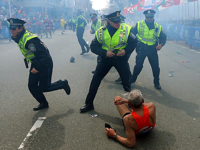Bill Iffrig, 78, lies on the ground as police officers react to a second explosion at the finish line. Iffrig, of Lake Stevens, Wash., was running his third Boston Marathon and near the finish line when he was knocked down by one of two bomb blasts. Picture: AP