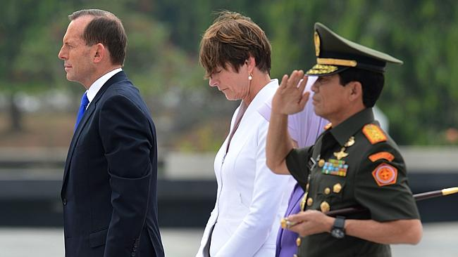 Prime Minister Tony Abbott stands with his wife Margie and an Indonesian military officer during a wreath laying ceremony at Kalibata Heroes' Cemetery in Jakarta.