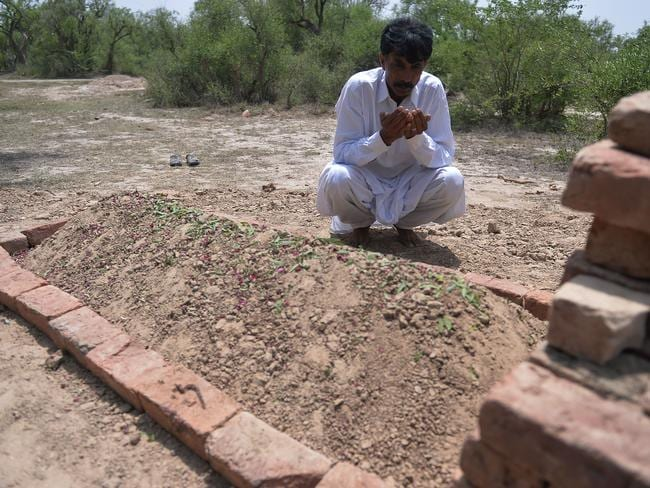 Mourning ... Iqbal prays at the grave of his murdered wife.