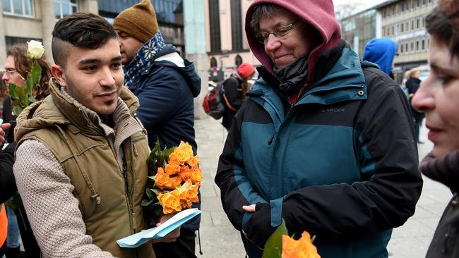 Refugees from Syria present flowers to passers-by as they demonstrate against violence near the Cologne main train station, two weeks after the New Year's Eve attacks. Picture: AFP/Patrik Stollarz