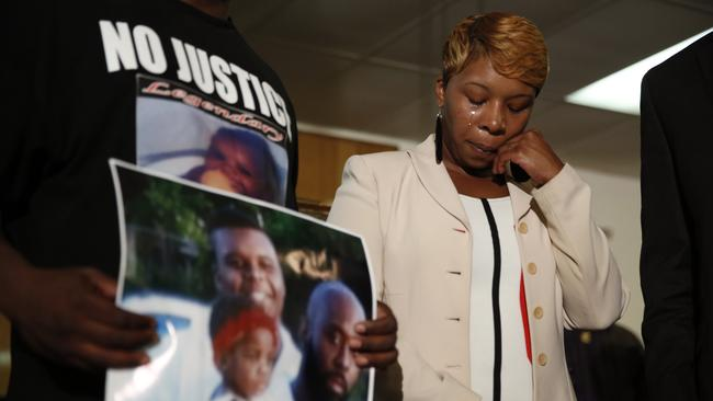 So much grief ... Lesley McSpadden, the mother of Michael Brown, wipes away tears as Brown's father holds up a family picture of himself, his son. Picture: AP Photo/Jeff Roberson