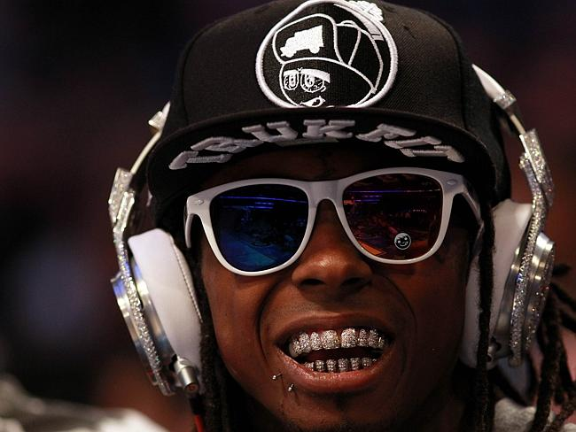 Lil' Wayne, wearing diamond studded beats headphones by Dr. Dre sits courtside during the