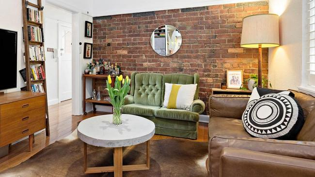 A brick feature wall stands out in the living room.