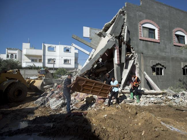 Helping hand ... people clear a house destroyed by an Israeli airstrike on Maghazi refugee camp in central Gaza. Picture: Mahmud Hams