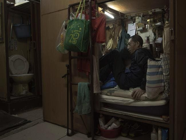 Wong Tat-ming, 63, sits in his 'coffin home' which is next to a set of grimy toilets in Hong Kong as he pays $420 a month for a compartment measuring three feet by six feet. It's crammed with all his meagre possessions, including a sleeping bag, small colour TV and electric fan. Picture: Kin Cheung/AP