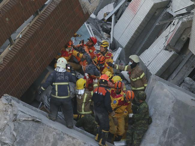 Rescue workers carry a 28-year-old Vietnamese woman, identified as Chen Mei-jih, rescued from the rubble of a collapsed building complex in Tainan.