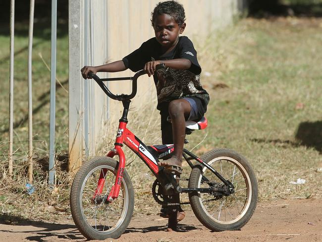 Indigenous boy Lewis Kooloika rides his bike through the dusty streets of Aurukun. Picture: Brendan Radke