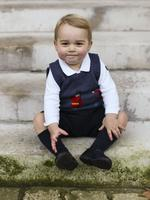 Britain's Prince George of Cambridge poses sitting in a courtyard at Kensington Palace in London. Three Christmas photos of a rosy-cheeked Prince George were released by Britain's royal family Saturday, offering a festive glimpse of the future king. Picture: AFP
