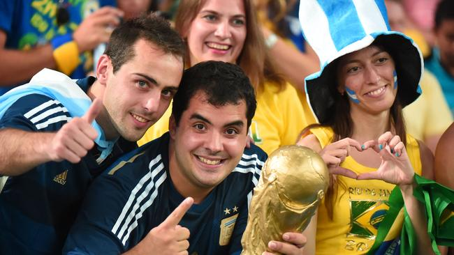Argentinian fans pose with a fake trophy before the match against Bosnia-Herzegovina at the Maracana in Rio.