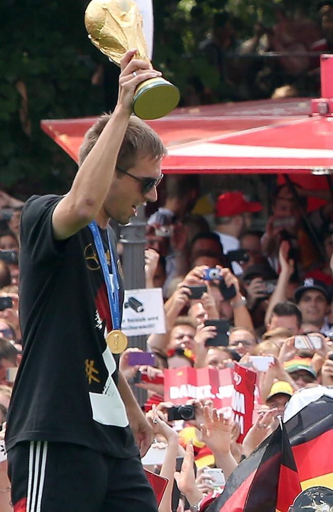 German captain Philippe Lahm holds the World Cup trophy as he celebrates with fans in Berlin.