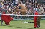 <p>Tournament referee Alan Mills and military steward attempting to catch naked male streaker jumping tennis net during mens singles final match at Wimbledon Championships 07 Jul 2002.</p>