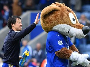 (FILES) This file photo taken on April 24, 2016 shows Leicester City's Japanese striker Shinji Okazaki (L) pats the Leicester City fox mascot after the final whistle of the English Premier League football match between Leicester City and Swansea at King Power Stadium in Leicester, central England. A glance around the press room before Leicester City's recent victory over Swansea City confirmed the extent to which their pursuit of Premier League glory has captivated global audiences. Journalists from as far afield as Finland, Turkey, South Korea and Australia mingled in the queue for a pre-match meal, while a 10-strong Japanese contingent sat around a table discussing how Shinji Okazaki would fare in the absence of his suspended strike partner Jamie Vardy. / AFP PHOTO / BEN STANSALL