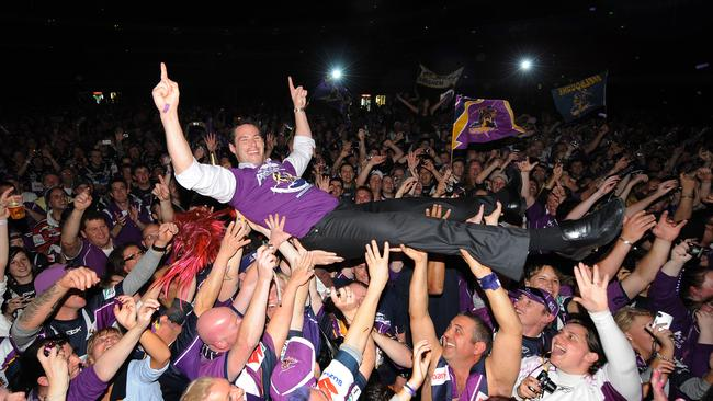 White enjoys some crowd surfing after the Storm's 2009 grand final victory.