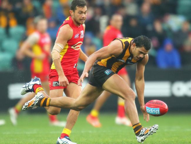 Cyril Rioli stretches for the ball ahead of Jarrod Harbrow. Photo by Scott Barbour