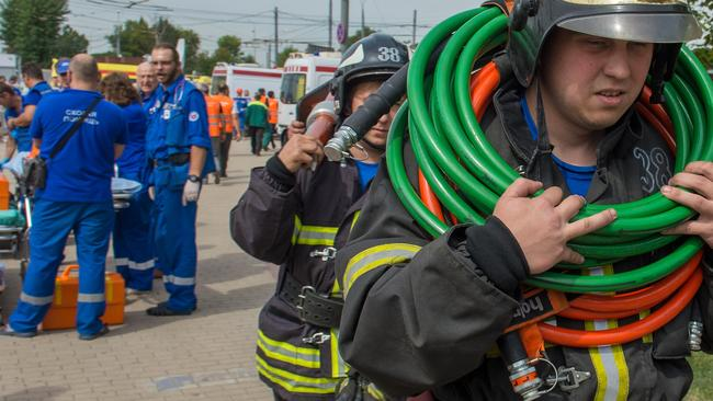Rescuers run ... to evacuate the passengers as several subway cars derailed in Moscow. Picture: DMITRY SEREBRYAKOV