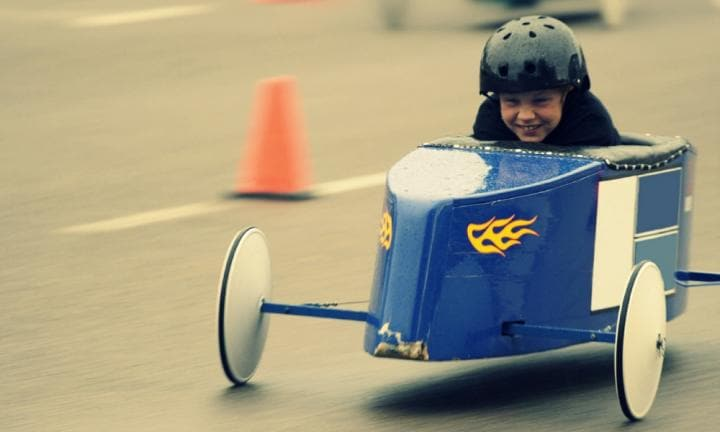 Boys driving soapbox race cars down a hill.