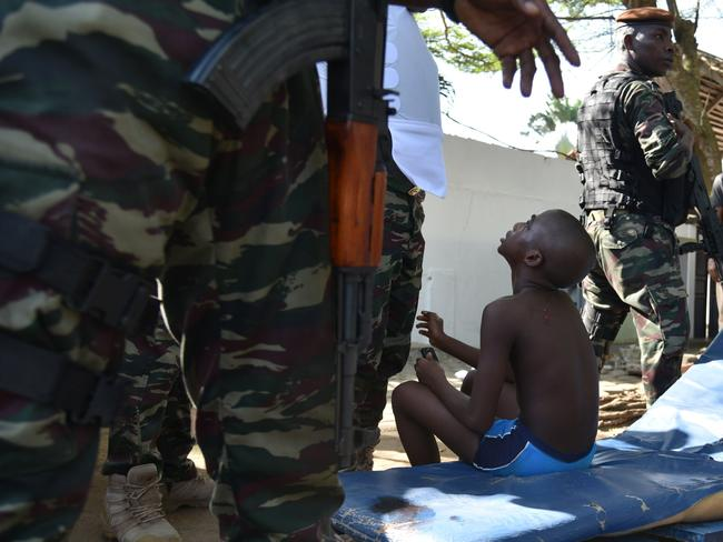 A wounded child is surrounded by Ivorian security forces after heavily armed gunmen opened fire on March 13, 2016 at a hotel in the Ivory Coast beach resort of Grand-Bassam.