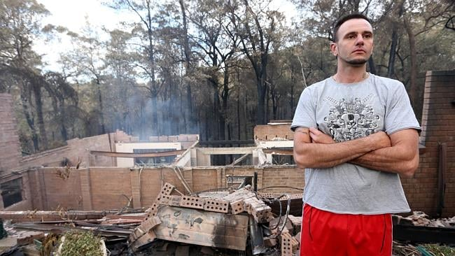 Nakia Belmer looks over his mothers destroyed home in Sunny Ridge Road, Winmalee.