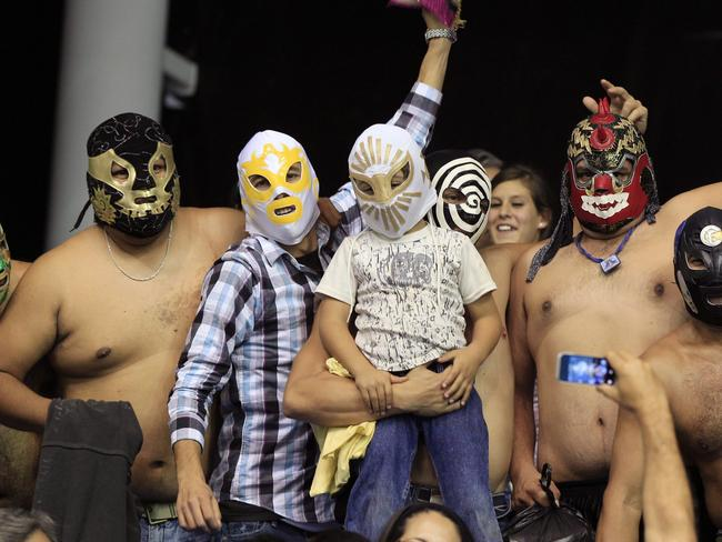 Fans wearing mask of wrestling fighters, known in Mexico as 'Luchadores', cheer for their team during a men's basketball match between Mexico and Argentina at the Pan American Games in Guadalajara, Mexico, 28/10/2011.