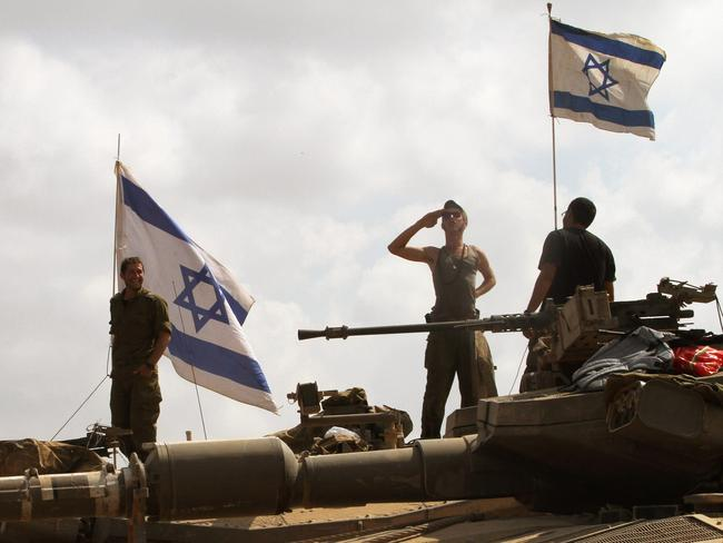 Tactical withdrawal ... Israeli soldiers stand on top of their Merkava tanks along the border between Israel and the Gaza Strip after they pulled out from the Gaza Strip on August 3, 2014. Picture: Gil Cohen-Magen