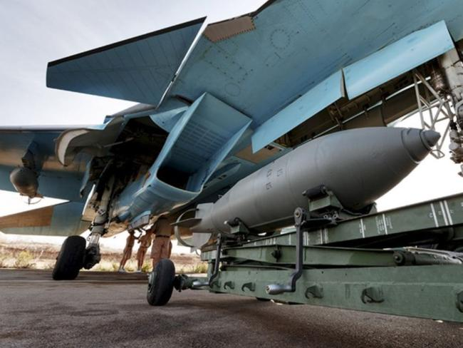 Russian ground staff members work on a Sukhoi Su-34 fighter jet at the Hmeymim air base near Latakia, Syria, in this handout photograph released by Russia's Defence Ministry.