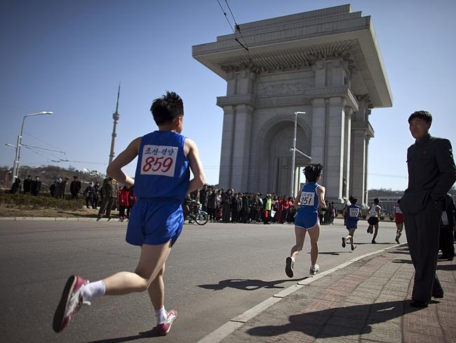 Triumph awaits ... people watch runners near the Arch of Triumph in Pyongyang during the 26th Mangyongdae Prize Marathon.