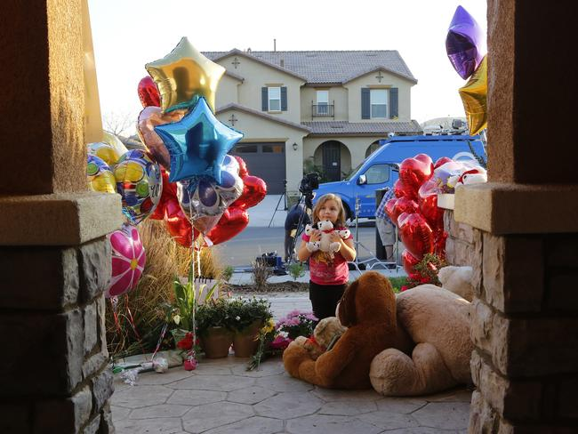 Neighbour Rilee Unger, 3, plays with a toy after dropping off a couple of her own teddy bears on the porch of a home where police arrested the Turpins. Picture: AP