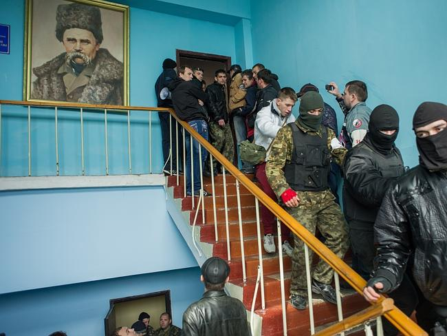 "Taking over...Crimean pro-Russian ""self-defence"" take over the Ukrainian navy headquarters, with a picture of 19th century Ukrainian poet and writer Taras Shevchenko, in Sevastopol, Crimea. Picture: AP"