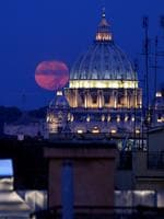 A red moon is seen behind the cupola (dome) of St Peter's basilica in Rome. Picture: Tiziana Fabi (AFP)