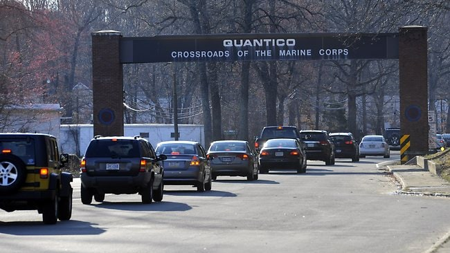 Cars pass under a sign at the entrance to the main gate at Quantico Marine Corps Base.