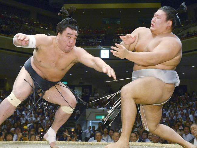In this Sept. 16, 2016, photo, Mongolian sumo grand champion Harumafuji, left, pushes opponent Takanoiwa out of the ring to win their bout at the Autumn Grand Sumo Tournament in Tokyo. Japanese media reported that Harumafuji hit his fellow Mongolian wrestler Takanoiwa in the head with a beer bottle at a party in October 2017, fracturing his skull base and causing other injuries. (Kyodo News via AP)