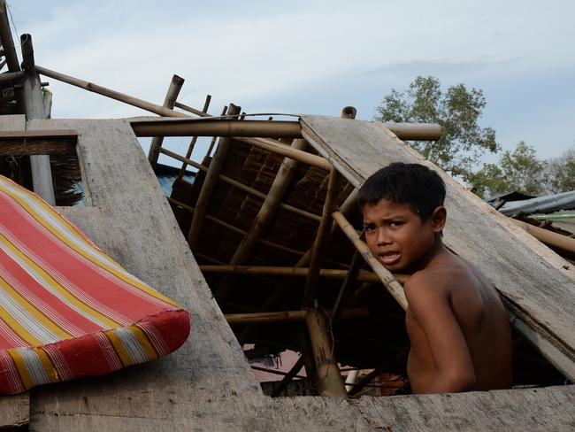 Earlier landfall ... A young boy sits in a house damaged by Typhoon Rammasun in Batangas, southwest of Manila, a day after the storm barrelled over the region. Picture: Ted Aljibe