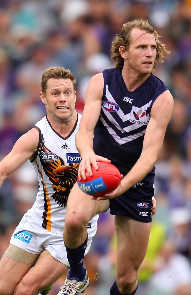 David Mundy, pictured ahead of Sam Mitchell in yesterday's win against the Hawks, would be well suited to playing International Rules, Clarkson says. Picture: Paul Kane/Getty Images