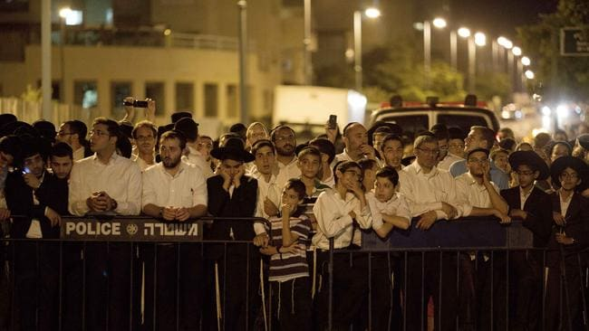 Vigil ... Orthodox Jews, family and friends of Israeli Eyal Yifrah, 19, one of three missing teenagers, gather out side of his home in Elad, central Israel, on Monday. Picture: AP/Ariel Schalit