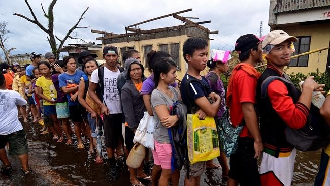 Survivors wait in line to receive relief goods in an area devastated by Typhoon Haiyan. (Photo by Dondi Tawatao/Getty Images)