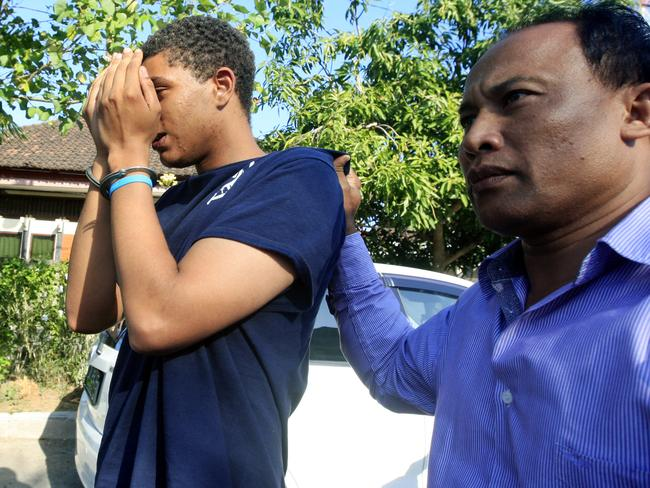 Under scrutiny ... an Indonesian police officer escorts Tommy Schaefer, left, as he is brought to the police station for questioning in relation to the death of his girlfriend's mother, in Bali, Indonesia. Picture: AP