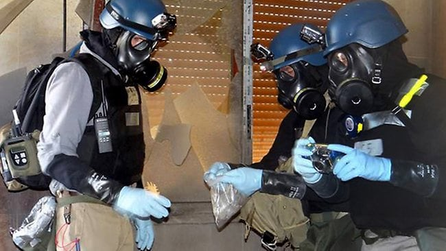 Mmembers of the UN investigation team take samples from the ground in the Damascus countryside of Zamalka, Syria.