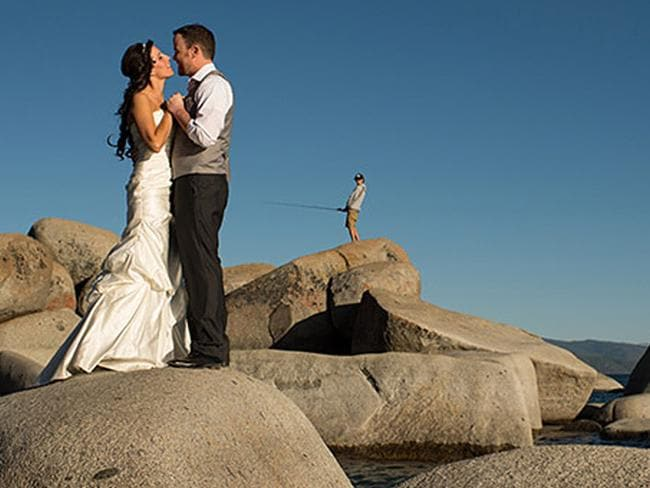 At first glance it's a lovely wedding photo of a loving couple. At second glance it's a lovely photo of a man fishing with a couple in the way. Picture: MATT THEILEN / ISPWP / CATERS NEWS