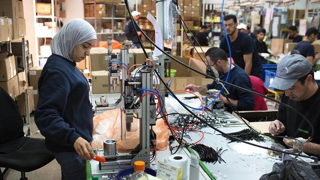 Palestinians work at a SodaStream factory next to the West Bank settlement of Ma'ale Adumim.