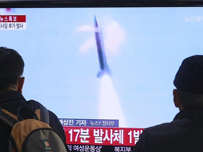 People watch a TV report about the North Korean missile test at Seoul Railway Station. Pi