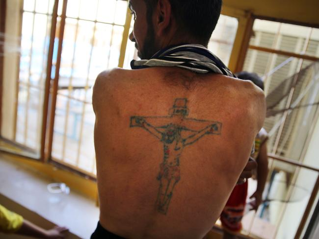 Displaced ... an Iraqi Christian displays a tattoo of Christ at Saint Joseph's church in Erbil where he is living with hundreds of other Christians forced to flee their homes. Picture: Spencer Platt
