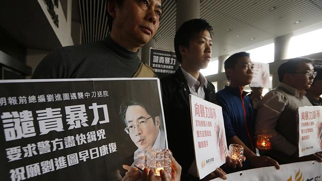 Fight...Pro-democracy protesters hold a picture of former Ming Pao editor Kevin Lau during a demonstration outside a hospital in Hong Kong. Picture: AP