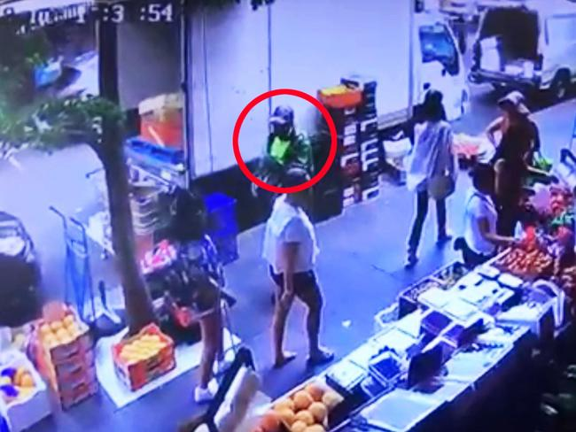The suspected shooter is seen in bright green on CCTV footage.